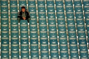 Ein einzelner Mann auf der Tribüne eines Sportstadions