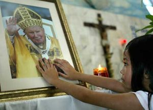 A young Malaysian touches a photograph of Pope John Paul II after a mass at a church in Kuala Lumpur, Malaysia, Sunday, April 3, 2005. Mass services at Catholic churches in Malaysia saw more parishes than usual Sunday following news of the Pope's death. (AP Photo/Teh Eng Koon)