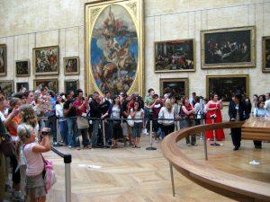 Vor der Mona Lisa im Louvre. Bilder sind mit vergoldeten Rahmen ausgestattet.